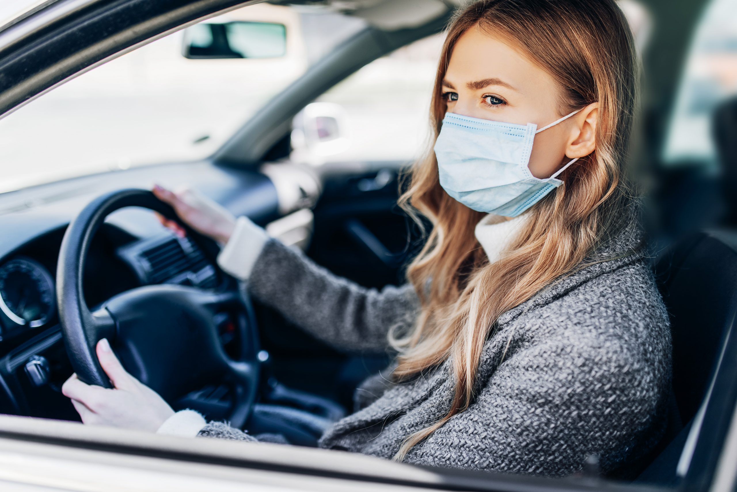 Beautiful young girl in a mask sitting in a car, protective mask against coronavirus, driver on a city street during a coronavirus outbreak